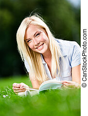 Woman reading book on the green grass
