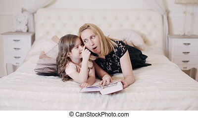 woman reading book to her daughter and kisses her