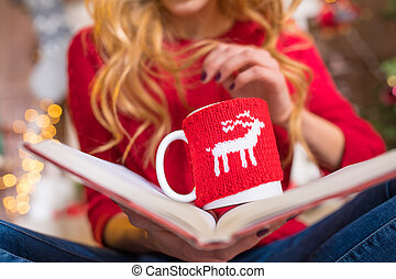 Woman reading book with hot drink