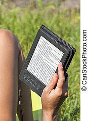 woman reading e-book outdoor in the summer