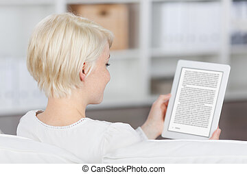 Woman Reading EBook - Closeup rear view of a blond young...