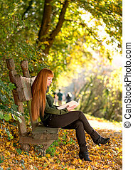 Woman reading in the autumn nature
