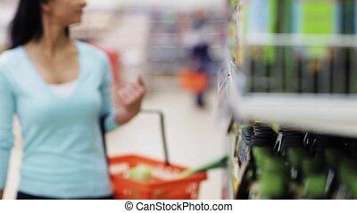 woman reading label on olive oil bottle at shop - sale,...