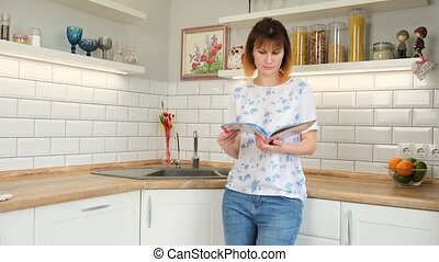 Woman reading magazine at kitchen table. Action. Redhead...
