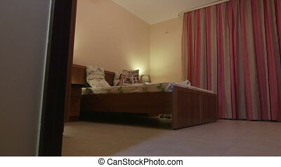 Woman reading magazine lying on bed in bedroom at home or hotel