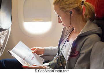 Woman reading magazine on airplane. - Woman reading magazine...