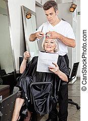 Woman Reading Magazine While Having Haircut