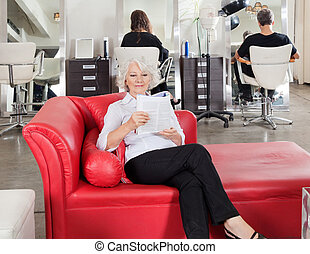 Woman Reading Magazine With Clients Waiting For Hairdresser