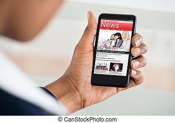 Woman Reading News On Mobile Phone