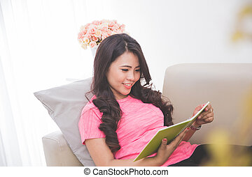 Woman reading notebook sitting on a couch and smiling