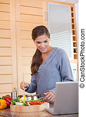 Woman reading off a recipe while cooking - Young woman ...