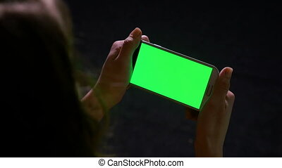 Woman reading online content on smart phone with green screen