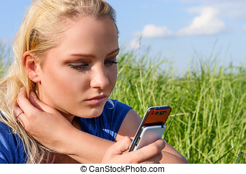 Woman reading sms - Young blonde woman reading sms on mobile...