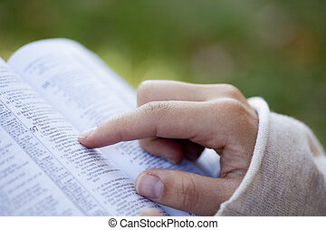 Woman Reading the Bible. - Close-up of woman's hands while...