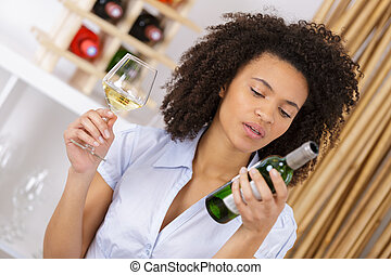 woman reading the bottle of wine label