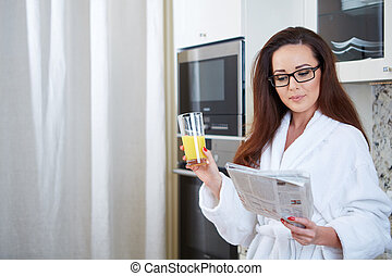 Woman reading the news while drinking orange juice