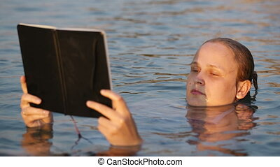Woman reading while floating in the sea