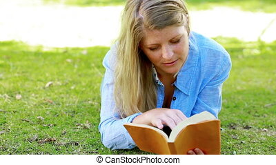 Woman reading while lying on front