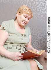 Woman reads a book at home