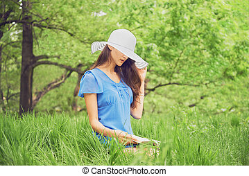 Woman reads a book in park