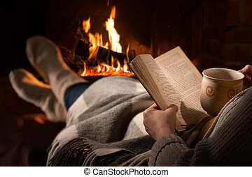 Woman reads book near fireplace - Woman resting with cup of ...