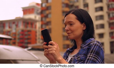 woman reads some information on her smartphone - lady using...
