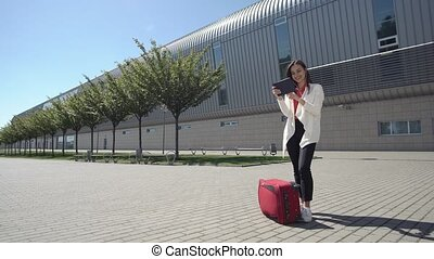 Woman reads something on her tablet standing with red suitcase