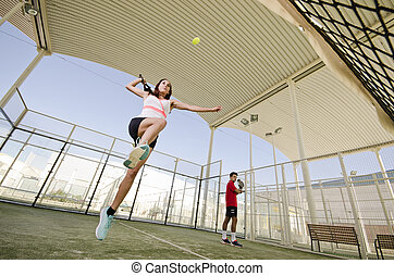 Woman ready for paddle tennis serve smash in court. Wide ...