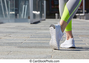 Woman ready to run in the city in a sunny morning