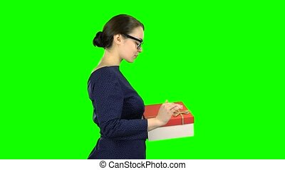 Woman received a gift and is glad. Green Screen. Side view -...