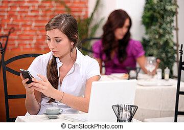 Woman receiving a text message in a restaurant
