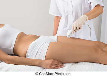 Woman Receiving Epilation Laser Treatment On Thigh At Beauty Clinic