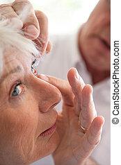Woman receiving eye drops