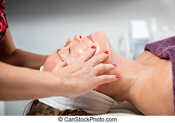 Side view of mature woman receiving face massage in beauty parlor