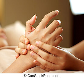 Woman receiving hand massage from a masseuse