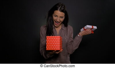 Woman receiving impressive gift and opening it happily and...