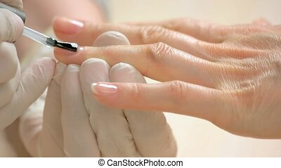 Woman receiving manicure in beauty salon. Close up...