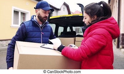 Woman receiving parcel from delivery man at the door. -...