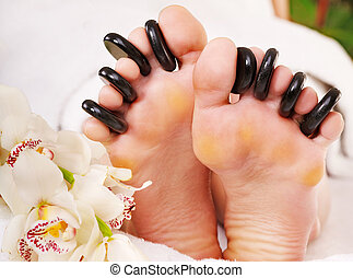 Woman receiving stone massage on feet. - Woman receiving hot...