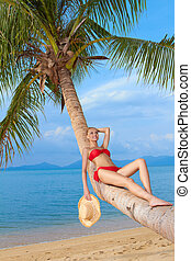 Woman reclining on a palm trunk