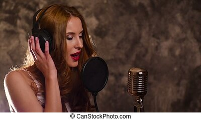 woman recording a song in music studio, slow motion, close up