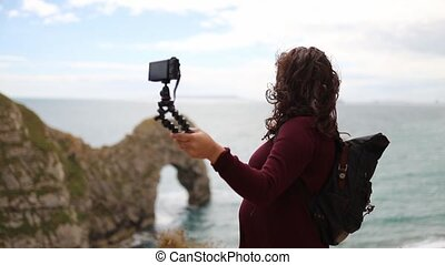 FHD video of a woman recording herself on the coastline looking at the ocean during a cloudy and windy day