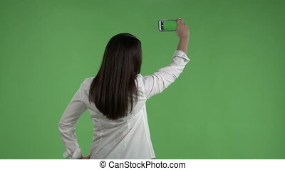 Woman recording video with her camera phone against a green screen