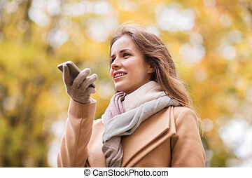 woman recording voice on smartphone in autumn park - season...