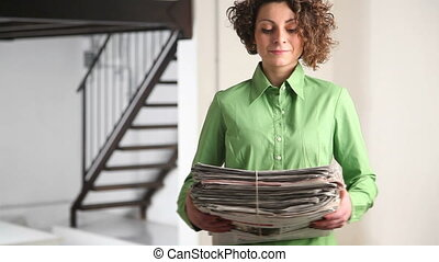 woman recycling newspapers - woman holding newspapers for...