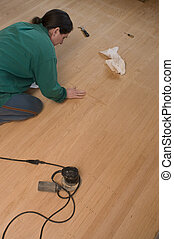 woman refinishing oak floors, applying filler