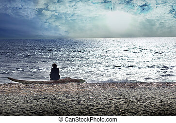 A solitary woman is comtemplating the sea on a mediterranean beach