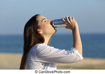 Woman refreshing drinking soda on the beach