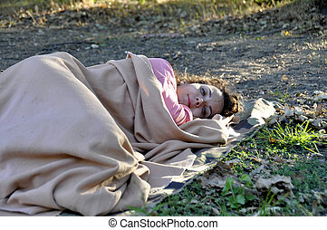 woman refugee sleeping on the ground covered with a rug