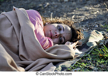 woman refugee sleeping on the ground covered with a rug.